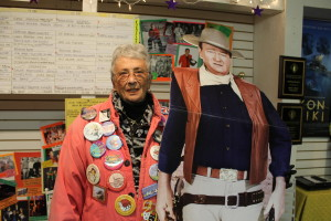 Letti Sullivan, one of the founders of First Night Chatham, poses with John Wayne, one of the cardboard cut-outs displayed during the Noise Parade as a tribute to the new Chatham Orpheum Theater, the new cinema that opened this year on Main Street thanks to an outpouring of community support. Sullivan wears buttons from all 23 years of the First Night Chatham event.