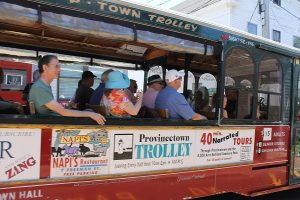 Tourists take a trolley ride down Commercial Street.