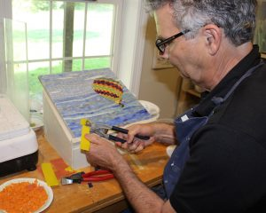 The artist uses a glass cutting tool to cut the pieces of stained glass.